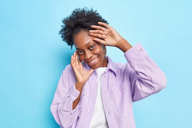 Studio-opname van een blije afro-amerikaanse vrouw met een donkere huid en een zachte, blije gezichtsuitdrukking voelt verlegen en kijkt recht in de camera