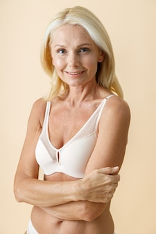 Studio-opname van een charmante rijpe vrouw met blond haar in wit ondergoed die naar de camera glimlacht terwijl