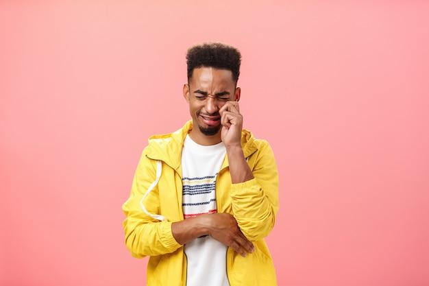 Studio-opname van een domme trieste afro-amerikaanse timide man in een geel trendy jasje huilend van hart, tranen uit de ogen en zeurend, zich eenzaam voelend nadat hij door ex-vriendin over roze muur is afgewezen