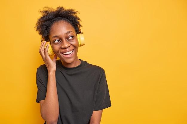 Studio-opname van een gelukkig millennial-meisje met krullend haar houdt de hand op de koptelefoon