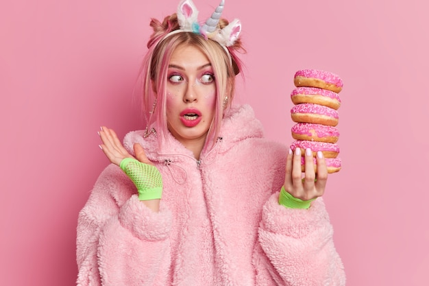 Studio-opname van een geschokte jonge europese vrouw die verrassend naar een stapel donuts staart en beseft hoeveel calorieën het bevat