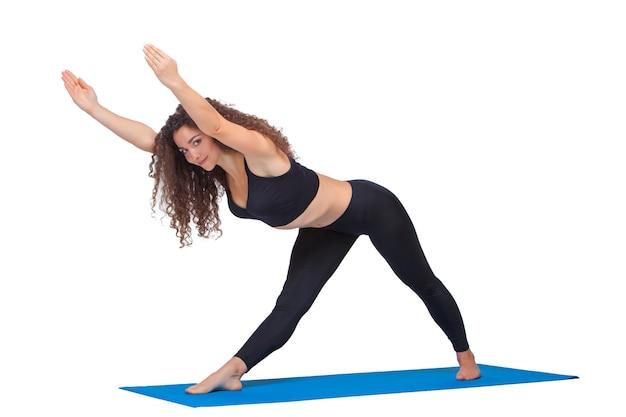 Studio-opname van een jonge fitte vrouw die yoga-oefeningen doet