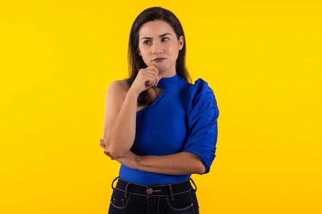 Studio-opname van een jonge vrouw in een bril met blauwe blouse op gele achtergrond met gezichtsuitdrukking