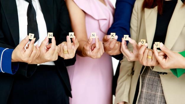 Studio-opname van een klein houten kubusblok bedankbrieven alfabetten die worden vastgehouden door onherkenbare niet-geïdentificeerde gezichtsloze vrouwelijke officierspersoneel in het bedrijfsleven draagt waardering voor collega's van klanten.