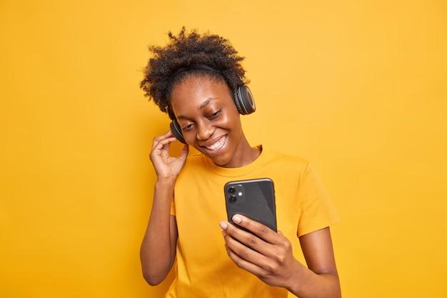 Studio-opname van een knappe vrouw met een donkere huidskleur geniet van favoriete afspeellijst en luistert naar muziek via een koptelefoon