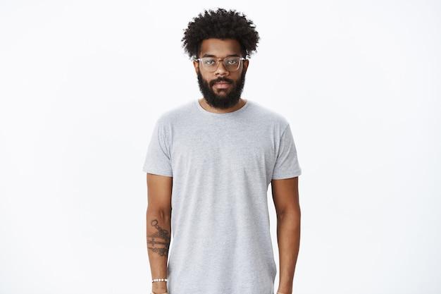 Studio-opname van een mannelijke afro-amerikaanse man met krullend haar en baard met een neusoorbel en een bril die naar voren kijkt met een kalme, ongedwongen uitdrukking in een gewone pose over een grijze muur