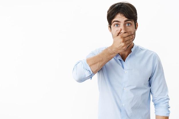 Studio-opname van een onzekere bezorgde knappe man met blauwe ogen en golvend donker haar die de mond sluit met de handpalm omdat hij bang is voor een slechte geur na het roken die nerveus over de grijze muur staat
