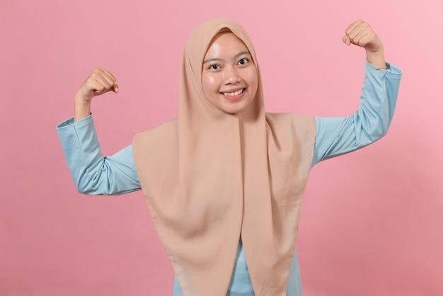 Studio-opname van een positieve jonge aziatische moslimvrouw die armen opheft, toont spieren die zich voordoen als zeer sterk en krachtig glimlacht en draagt zachtjes hijab geïsoleerd over roze achtergrond.