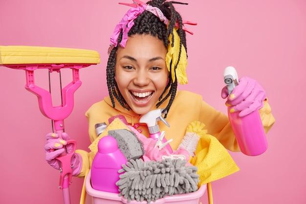 Studio-opname van een positieve vrouw met een donkere huid die de glimlach van een appartement schoonmaakt en graag dweil en schoonmaakmiddel vasthoudt