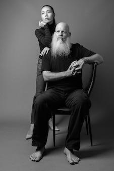 Studio-opname van een volwassen, bebaarde kale man en jonge mooie aziatische vrouw samen tegen een grijze muur in zwart-wit Premium Foto