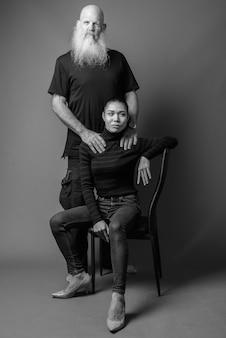 Studio-opname van een volwassen, bebaarde kale man en jonge mooie aziatische vrouw samen tegen een grijze muur in zwart-wit