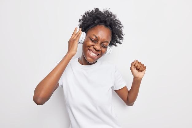 Studio-opname van een vrolijke jonge vrouw met een donkere huidskleur terwijl ze naar muziek luistert in een koptelefoon danst en