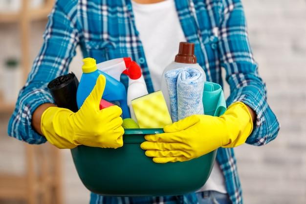 Studio-opname van huishoudster tijdens het schoonmaken van de kamer. vrouw die handschoenen draagt, duim opsteekt en een kom vol flessen met ontsmettingsmiddel vasthoudt