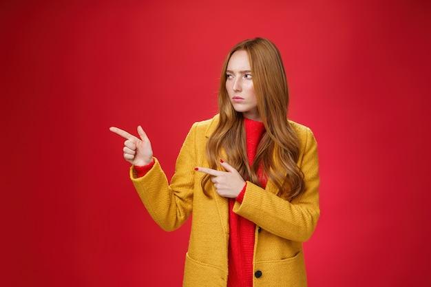 Studio-opname van intens verdachte en ontevreden roodharige vrouw in gele jas, wijzend en kijkend...