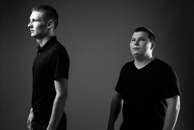 Studio-opname van jonge man en jonge man met overgewicht samen tegen zwarte muur in zwart-wit black