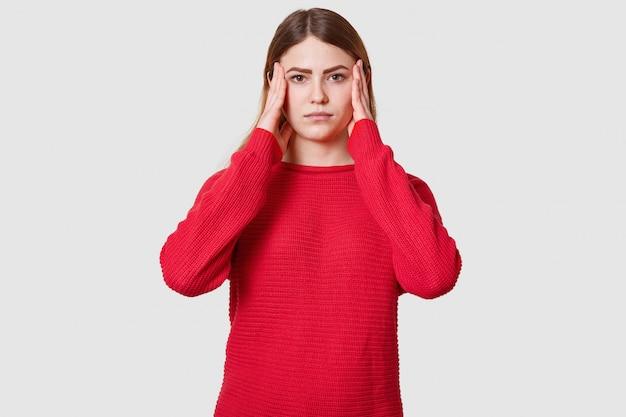 Studio-opname van ontevreden vrouw lijdt aan hoofdpijn, gekleed in rode trui, houdt handen op tempels, heeft gezichtsuitdrukking van streek gemaakt