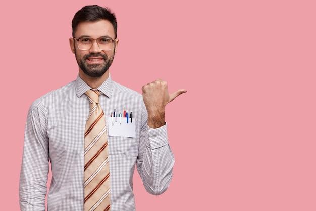 Studio-opname van positieve ongeschoren europese jongeman wijst met duim opzij, toont resultaat van zijn ijverig werk, voelt zich trots