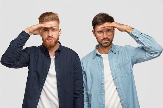 Studio-opname van serieuze jongens houden hun handen bij het voorhoofd, kijken serieus in de verte, proberen iets ver weg te zien