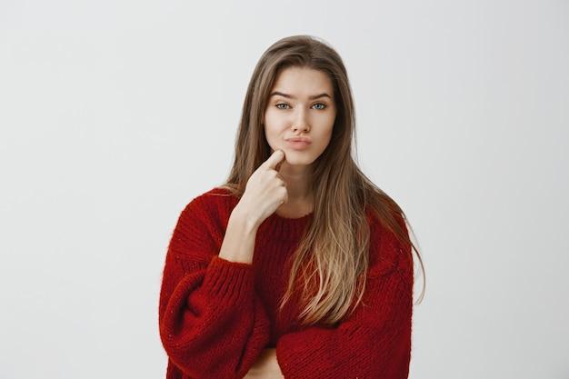 Studio-opname van teleurgestelde blanke vrouw in rode losse trui, vinger op kin en pruilend, ontevreden en twijfelachtig kijkend, iets oninteressants ziet