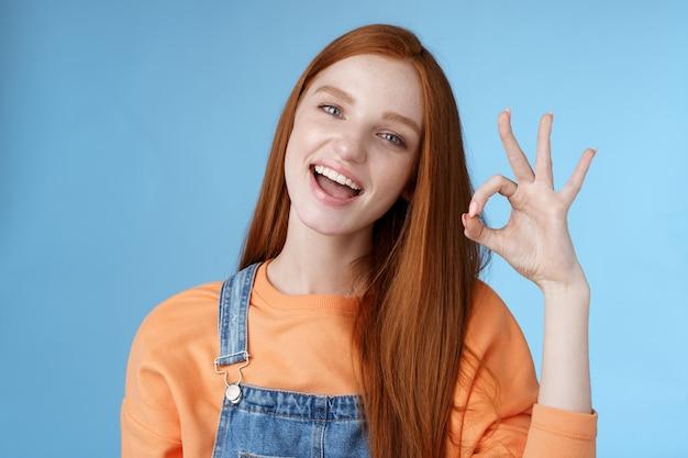 Studio-opname zorgeloos gelukkig aantrekkelijk europees roodharig meisje laten zien oke ok teken lachend witte tanden goedkeuring bevestiging aanbevelen goed product eens voorwaarden geven positieve feedback, denk idee perfect.