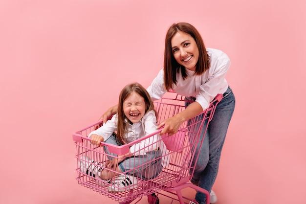 Studio portret van aantrekkelijke europese vrouw met haar kleine meisje, zittend in roze winkelmandje met gesloten ogen