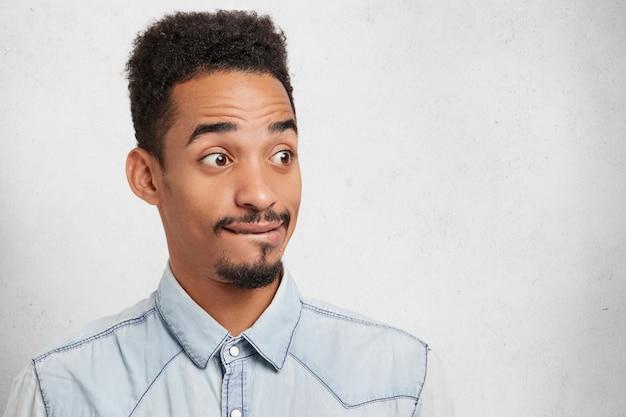 Studio portret van aantrekkelijke man met een specifiek uiterlijk, kijkt met afgeluisterde ogen, heeft peinzende uitdrukking,