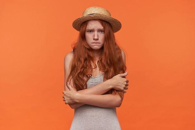Studio portret van bange jonge mooie roodharige vrouw permanent over oranje achtergrond met gevouwen handen, op zoek naar camera nauwelijks en rimpelend voorhoofd