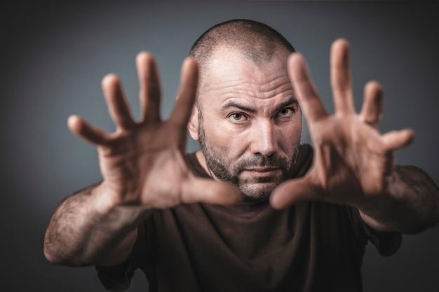 Studio portret van blanke man met open handen en uitgestrekte armen naar voren.