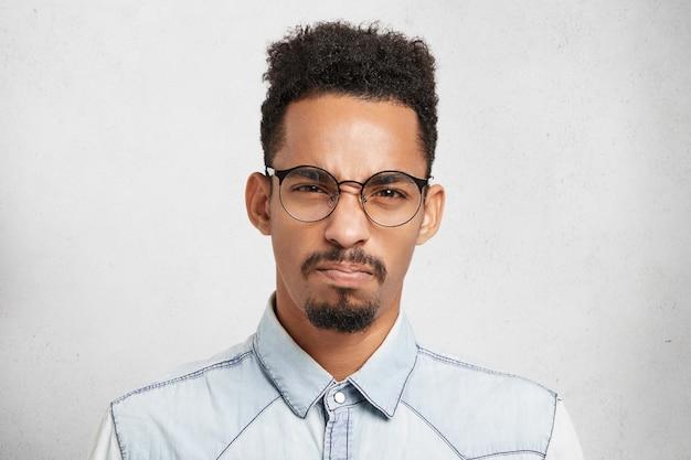 Studio portret van chagrijnig stijlvolle jongeman fronst gezicht met ontevredenheid, heeft een slecht humeur, voelt zich woedend en geïrriteerd door iets