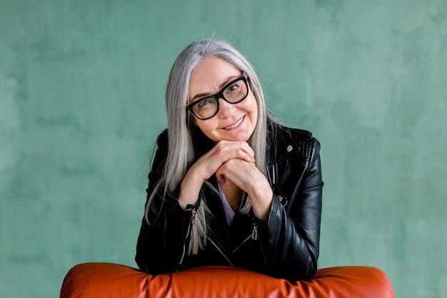 Studio portret van charmante senior moderne dame in brillen, met lang recht grijs haar, trendy zwart lederen jas, die poseren op camera met een glimlach