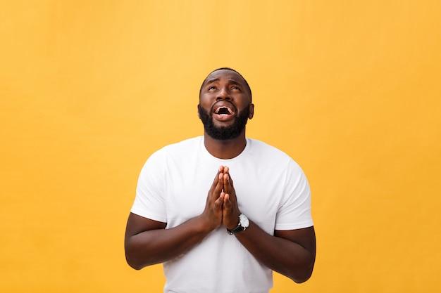 Studio portret van de jonge african american man in wit overhemd, hand in hand in het gebed