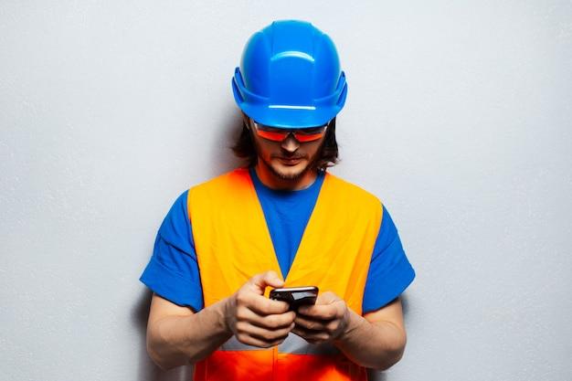 Studio portret van een jonge man, bouwvakker ingenieur, met behulp van smartphone dragen veiligheidsuitrusting op de achtergrond van grijze muur.