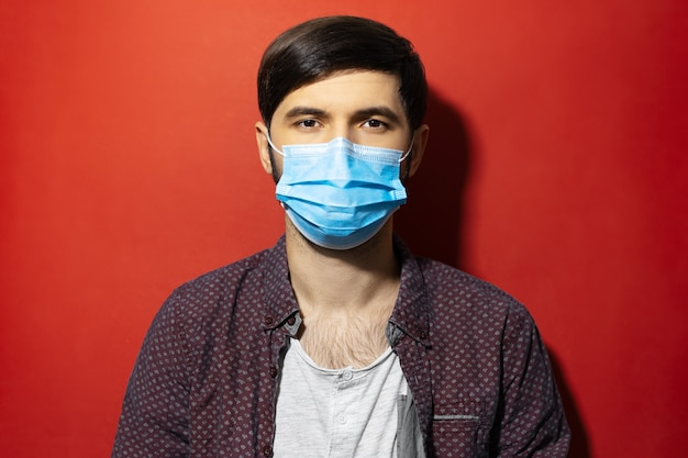 Studio portret van een jonge man met medisch gezichtsmasker tegen coronavirus op rode achtergrond.