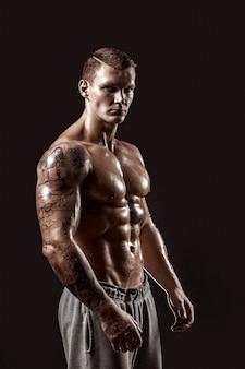 Studio portret van een shirtless atletische getatoeëerde man
