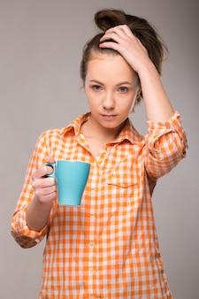 Studio portret van een slaperige vrouw in een oranje shirt met een kopje koffie in de hand
