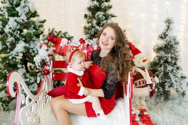 Studio portret van gelukkige moeder en dochter in santa's doeken zitten in de buurt van kerstboom