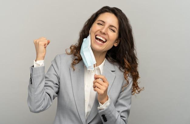 Studio portret van gelukkige zakenvrouw opstijgen masker, vuist, grijze achtergrond opheffen. vrouw medische masker verwijderen uit gezicht en camera kijken. coronavirus, covid-19 eindigde.