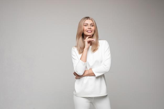 Studio portret van glimlachende blonde aantrekkelijke vrouw in wit pak geïsoleerd op een grijze achtergrond