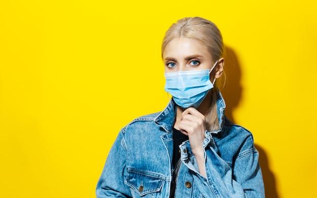 Studio portret van jong blond meisje in denim jasje, medische gezichtsmasker dragen tegen coronavirus op gele achtergrond met kopie ruimte.
