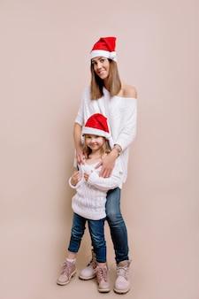 Studio portret van jonge aantrekkelijke vrouw met haar kleine dochter, gekleed in witte truien en kerstmutsen