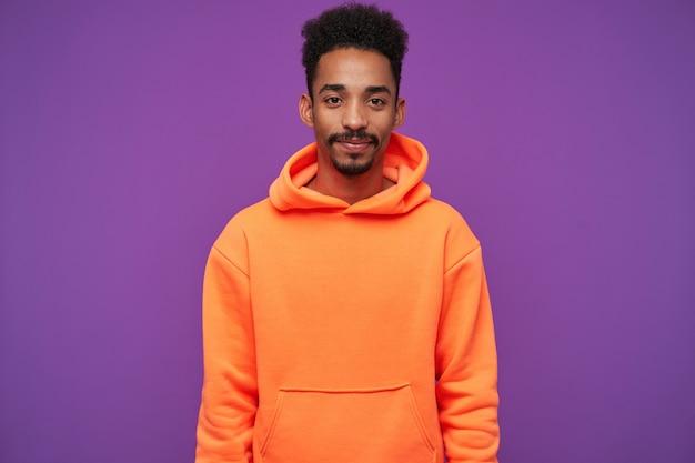 Studio portret van jonge bebaarde donkere huid krullend brunette man houden lippen gevouwen terwijl posiyively kijken, oranje hoodie dragen op paars