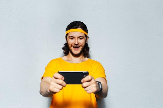 Studio portret van jonge gelukkig man in geel met lang haar, speelspel op smartphone op grijze achtergrond.