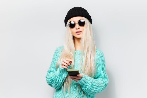 Studio portret van jonge hipster blonde meisje met behulp van smartphone op witte achtergrond. het dragen van een ronde zonnebril en een zwarte muts.