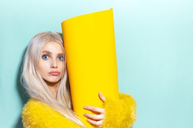 Studio portret van jonge opgewonden meisje met grote gele papierrol in handen. achtergrond van cyaan, aqua menthe kleur. Premium Foto