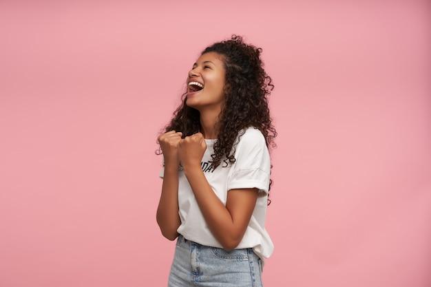 Studio portret van jonge vrolijke donkere huid vrouw vreugde over iets met opgeheven vuisten, gelukkig lachend en op zoek naar boven, poseren op roze in vrijetijdskleding