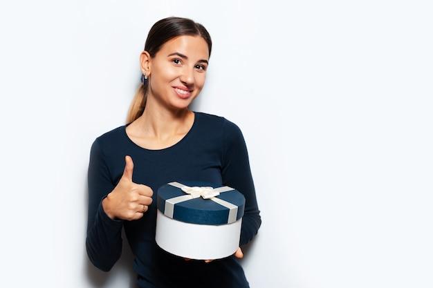 Studio portret van jonge vrouw met een geschenkdoos op oppervlak van witte kleur. duim opdagen