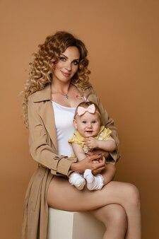 Studio portret van mooie blanke moeder met lang golvend haar, gekleed in beige klassieke geul en witte top met schattige baby dochter in armen zittend op wit tegen perzik muur.