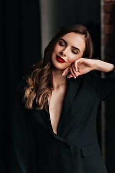 Studio portret van mooie vrouw met rode lippen en golvend haar dragen zwarte jas poseren