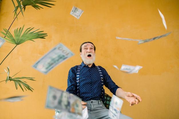 Studio portret van opgewonden vrolijke knappe oudere man in stijlvolle kleding, met goed verzorgde baard, en open mond, die onder papiergeld regen zit