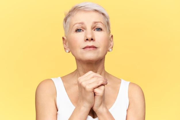 Studio portret van overstuur gepensioneerde blanke vrouw met wanhopige treurige blik, handen gevouwen op de borst, biddend, haar hart gevuld met geloof en overtuiging, wachtend op wonder. lichaamstaal